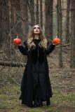 万圣节 美丽的女孩用在一件黑礼服的一个南瓜在森林里 免版税库存照片