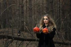万圣节 美丽的女孩用在一件黑礼服的一个南瓜在森林里 免版税图库摄影