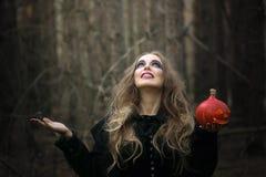万圣节 美丽的女孩用在一件黑礼服的一个南瓜在森林里 免版税库存图片