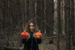 万圣节 美丽的女孩用在一件黑礼服的一个南瓜在森林里 图库摄影