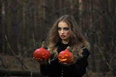 万圣节 美丽的女孩用在一件黑礼服的一个南瓜在森林里 库存照片