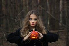万圣节 美丽的女孩用在一件黑礼服的一个南瓜在森林里 库存图片