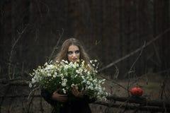万圣节 领域春黄菊 一件黑礼服的美丽的女孩在森林里 免版税库存图片