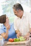丈夫一起准备妻子的膳食进餐时间 图库摄影