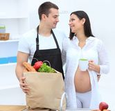 丈夫和他怀孕的妻子通过组装梳,站立在厨房里 免版税库存照片