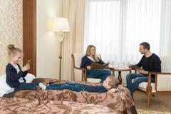 丈夫和妻子和孩子在旅馆客房 孩子坐床,在椅子的父母 年轻 免版税库存照片