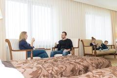 丈夫和妻子和孩子在旅馆客房 孩子坐床,在椅子的父母 年轻 免版税库存图片