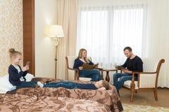 丈夫和妻子和孩子在旅馆客房 孩子坐床,在椅子的父母 年轻 免版税图库摄影