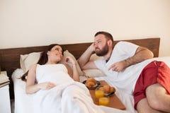 丈夫和妻子在卧室周末早餐的早晨醒在床上 免版税图库摄影