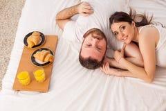 丈夫和妻子在卧室周末早餐的早晨醒在床上 库存照片