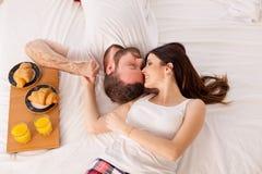 丈夫和妻子在床上早晨在床上醒用早餐 免版税库存图片