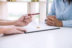 丈夫和妻子读离婚协议和归档的笔对签署的离婚判决溶解或取消  免版税图库摄影