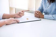 丈夫和妻子读离婚协议和归档的笔对签署的离婚判决溶解或取消  免版税库存图片