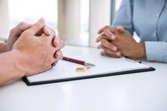 丈夫和妻子读离婚协议和签署的离婚判决婚姻屑子的溶解或取消 免版税库存图片