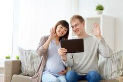丈夫和怀孕的妻子有片剂个人计算机的在家 库存照片