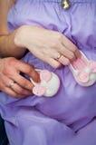丈夫和妻子、妈妈和爸爸握有赃物的手在腹部 怀孕 库存照片