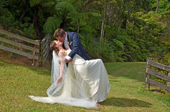 丈夫和妻子亲吻在户外他们的婚礼之日 免版税库存照片