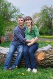 丈夫和他怀孕的妻子坐一个木甲板 免版税库存图片