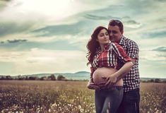 丈夫和他怀孕的妻子走在sunse 免版税库存照片
