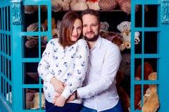 丈夫在儿童的玩具背景中的拥抱他怀孕的妻子  库存照片
