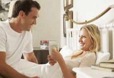 丈夫在床上的在家带来妻子热的饮料 免版税库存图片