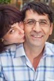 丈夫对妻子的亲吻爱 免版税库存照片