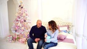 丈夫对妻子的` s爱的新年` s礼物的显示和介绍,坐床在有圣诞节的卧室 股票视频