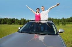 丈夫,在汽车舱口盖的妻子姿势  免版税库存照片