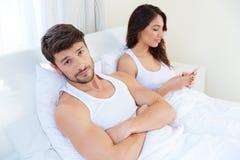 丈夫,当他的互联网上瘾者妻子使用手机时 免版税库存图片