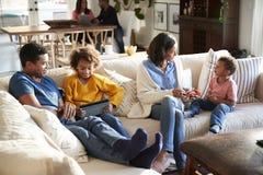 三一代花费时间在他们的开放学制客厅,祖父母的家庭家庭在背景,高的看法中 库存照片