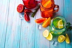 三上色了玻璃用柑橘柠檬水和切片在蓝色背景的果子 免版税库存图片