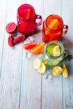 三上色了玻璃用柑橘柠檬水和切片在蓝色背景的果子 库存照片