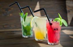 三不同刷新的柠檬水用柠檬和石灰在木背景 玻璃水瓶柑橘饮料冰橙色夏天水 库存图片