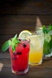 三不同刷新的柠檬水用柠檬和石灰在木背景 玻璃水瓶柑橘饮料冰橙色夏天水 库存照片