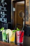 三不同刷新的柠檬水用柠檬和石灰在酒吧的背景在咖啡馆 玻璃水瓶柑橘饮料冰橙色夏天水 库存照片