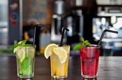 三不同刷新的柠檬水用柠檬和石灰在酒吧的背景在咖啡馆 玻璃水瓶柑橘饮料冰橙色夏天水 免版税图库摄影