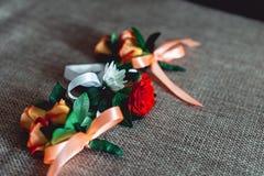 三与玫瑰的一点婚礼钮扣眼上插的花与丝带 免版税库存照片