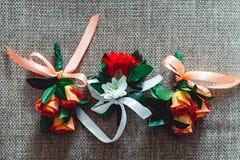 三与玫瑰的一点婚礼钮扣眼上插的花与丝带 库存照片