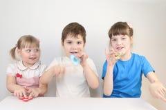 三与锭床工人的愉快的儿童游戏在桌上 免版税库存图片