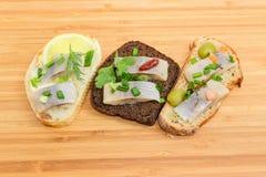 三个不同单片三明治用在切口的烂醉如泥的鲱鱼 免版税库存图片