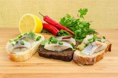 三个不同单片三明治用在木s的烂醉如泥的鲱鱼 免版税库存照片