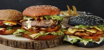 三个不同开胃汉堡在桌上 库存照片