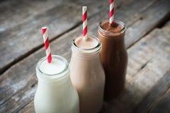 三个不同排序饮料瓶木背景 免版税库存图片