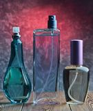 三个不同瓶在一个木架子的香水以一个混凝土墙为背景 库存照片