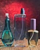 三个不同瓶在一个木架子的香水以一个混凝土墙为背景 库存图片