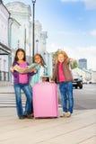 三个与地图和行李的微笑的女孩立场 库存图片