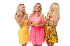 三个与蛋糕和香槟的白肤金发的女孩庆祝生日 库存图片