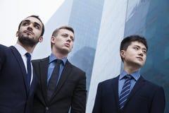 三个严肃的商人画象,户外,商业区 免版税库存照片