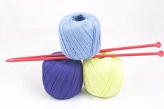 三个五颜六色的丝球和编织针 免版税库存图片