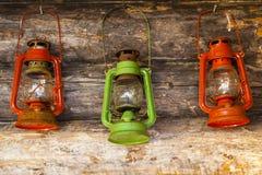 三个五颜六色的灯或灯笼在原木小屋 免版税库存照片